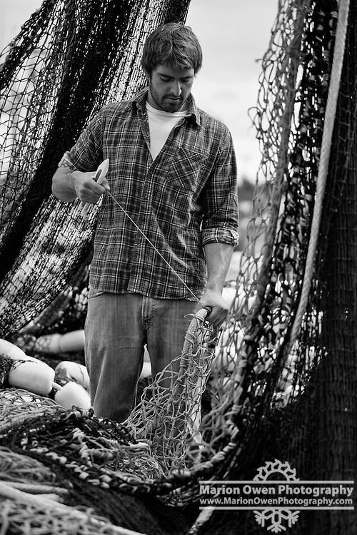 Fisherman mending commercial salmon seine net in Saint Paul Harbor, Kodiak Island, Alaska, summer
