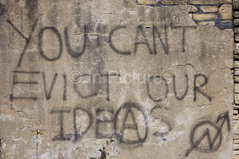 Graffiti sprayed on a rendered brick wall proclaims that a higher authority 'Can't evict our ideas'. This message of resistance by the underdogs of a moral majority appears on a part of wasteland in the Yorkshire city of Bradford, where the residents of an estate near the city centre have been forcibly removed to make space for a new development. Before their migration, the anonymous, downtrodden people were desperate enough to write this piece of anarchical philosophy that might be seen as a metaphor for a class war against the establishment by The People; the working classes otherwise known in Marxist ideology, as the Proletariat – a kind of thought from the (Orwellian) novel Nineteen Eighty-Four, by George Orwell.