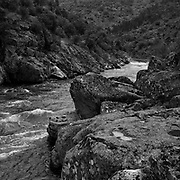 DUR DURIS<br /> <br /> That day, the youngest of three brothers was the last to wake up. It was called Douro and awoke with a start, from a sleep that only do the rivers and, to date, only legends could witness. While the brothers Tejo and Guadiana, could quietly stream down the mountain, choosing softer land and plains, the Douro had to face the hard way, through the rocky canyons of northern Portugal.<br /> Today, these images take the same stony path, perhaps to prevent that the river falls asleep. The construction of large dams tamed the course of the Douro, but in the riverbanks, the legend continues to endure with the eternal confrontation and dialogue that carved the rock, the mountain and the man.<br /> Distant from the route of the river cruises where the water is just one more road, flat, between floodgates. I preferred to embark on a counter-current journey along the Douro and its tributaries (Támega, and Corgo).<br /> <br />  Still life or artificial construction that with time became simple artifice. A journey in search of the humans transformed by the rock and a landscape petrified by the absence of local people.<br /> The course of the river is the only thread of this route without a guide, where the mirror-like waters may be merely a reflection of its inhabitants. Waking up late but waking up on time to track down this river that carved rocks and dilutes people in hard (Duris in Latin) water (Dur in Celtic). <br /> <br /> Tua River.