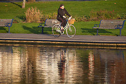 © Licensed to London News Pictures. 30/10/2017. Southsea, UK.  A woman riding her bike along Southsea Canoe Lake on a sunny but cold morning, 30th October 2017.  Photo credit: Rob Arnold/LNP
