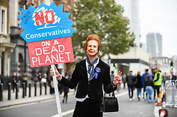 © Licensed to London News Pictures. 08/10/2019. LONDON, UK.  A climate activist dressed as Margaret Thatcher, walks down Whitehall outside Downing Street, on day two of Extinction Rebellion's protest which is planned to close-down Westminster and other areas in the capital for two weeks.  Demonstrators are calling on the Government's immediate action to tackle the negative effects of climate change.  Photo credit: Stephen Chung/LNP