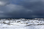 A brief patch of sun illuminates the windswept and snow-covered lava fields of the south coast of the Snaefellsnes Peninsular, between Búðir and Arnastappi, Western Iceland