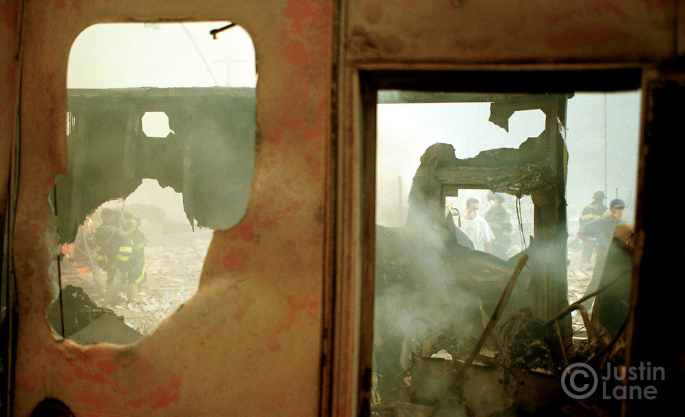 09/11/01--New York, NY--<br />Picture from ground zero of the World Trade Center destruction. Firefighters and other resuce workers are seen through the burned out ruins of an ambulance.<br />PHOTOGRAPH BY JUSTIN LANE