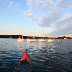 The bow of a kayak and moored sailboats in Portsmouth Harbor in Portsmouth, New Hampshire.