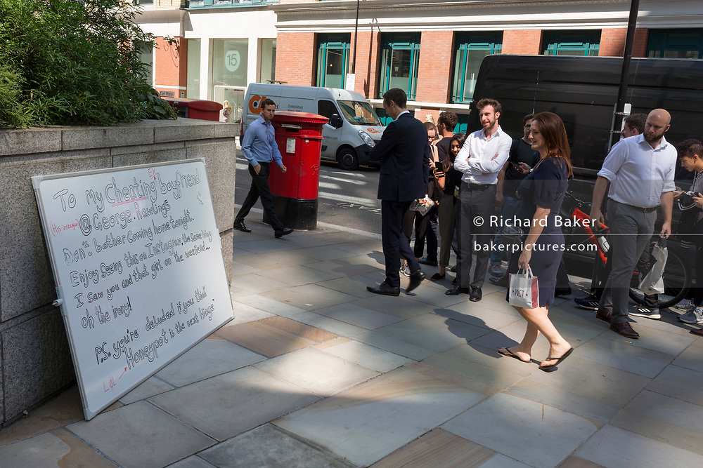 City workers take interest in a white-board through Broadgate that purports to be written by a jealous lover to her cheating partner who works nearby but is actually part of a new Dating app start-up's PR stunt in the City of London, the capital's financial district - aka the Square Mile, on 8th August, in London, England.