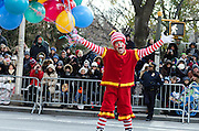 Crowds waiting for the Macy's Thanksgiving Day Parade to start are entertained by rollerskating clowns.