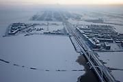 Nederland, Noord-Holland, Amsterdam, 07-01-2010; winterlandschap met IJburg, Steigereiland en Haveneiland, Enneus Heermabrug in de voorgrond.De lucht laat zogenaamde inversie zien (temperatuuromkering): door het winterweer - met vorst - is er aan het aardopppervlak koude lucht. Deze lkoude lucht wordt vastgehouden door de dunne warme luchtlaag daar boven; hierdoor ontstaat mist en kan ook ook luchtverontreiniging gevangen gehouden worden (ontstaan smog) .Winter landscape with IJburg. In the air so-called inversion (temperature inversion): cold air on ground level (as a result of to the frosty winter weather), above it a thin warm air layer which prevents the cold air, with fog and pollution, to move upward .luchtfoto (toeslag), aerial photo (additional fee required).foto/photo Siebe Swart