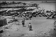 Local people descend to beached pirogues that line the inland river port of Mopti, where the Bani and Niger Rivers meet, in the semi-arid Sahel region of Mali in West Africa.  The very existence of human settlement in the western Sahel region is dependent on the seasonal rains that feed their lifeline, the Niger River.