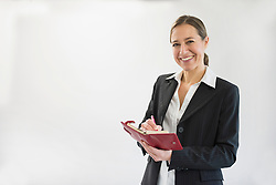 Portrait of businesswoman in black suit holding notebook and pen, smiling