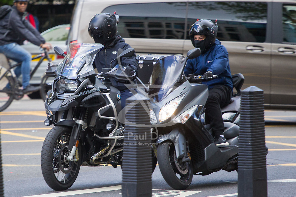 Suspected motorcycle thieves are seen on the Marylebone Road passing Westminster Magistrates Court. These gangs usually work in threes, cutting the target motorcycle's lock with an angle grinder, with one of them deterring interference from passersby, before using a powerful scooter to push the stolen bike - in this case a BMW GS R 1200 through the traffic to a waiting van. This particular group ran a red light causing traffic to swerve to avoid them as they used their hooter to warn oncoming traffic before continuing west towards Edgeware Road, swerving and weaving through slow moving traffic. London, May 01 2018.