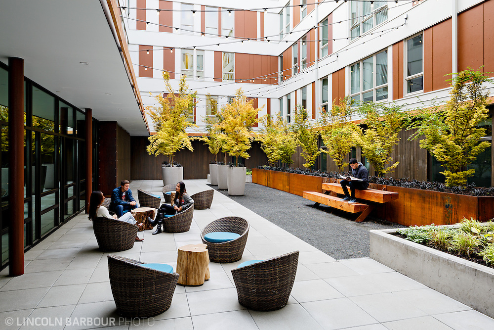 University House student housing apartment in Eugene, OR. Designed by Mahlum Architects.  A modern design courtyard with students engaging in conversation and another reading.
