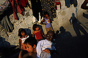 Roma autistic child playing in ghetto with black doll. The mentally handicapped are well looked after and integrated within their community. Kagithane district, Istanbul Turkey 2006