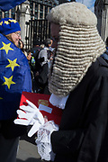 A newly-appointed QC Queens Council aka silk in legal vernacular leaves the House of Commons the UK parliament and stands next to a pro-Europa Protestor after being sworn to his latest legal position, on 11th March 2019, in London, England.