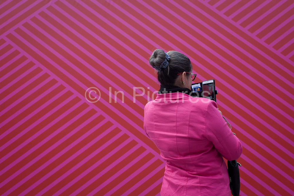 Girls and pink background of main venue for London Fashion Week at Somerset House. A bright pink background is featured on the exterior of the main venue for catwalk shows by the world's major designers and visitors to the shows wait outside and pose for pictures against the backdrop.
