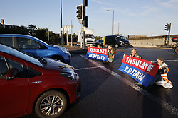 © Licensed to London News Pictures. 04/10/2021. London, UK. Activists from Insulate Britain climate change protest group block the Hangar Lane gyratory on the A40 junction with the North Circular in West London.  Harsher punishments are to be introduced by the government to deal with climate change activists, who continue to block motorways and major roads causing disruption. Home Secretary Priti Patel is expected to warn protestors they could face unlimited fines and up to six months in jail. Police will also be given powers to stop and search activists for equipment used to prevent them from being cleared from the road such as glue and locks. Photo credit: Peter Macdiarmid/LNP