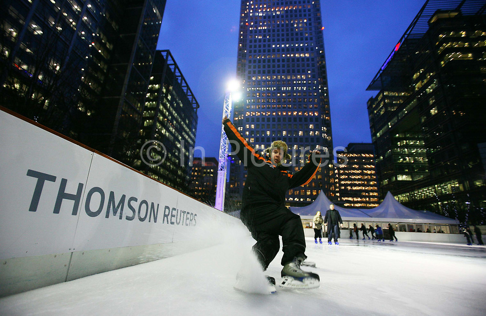 People enjoying some ice skating at the Canary Wharf Ice Rink, London, UK. Ice rinks have become a popular winter activity around the Christmas season in the UK. Ice Rink Canary Wharf offers the chance to skate beneath Canary Wharf's striking architectural backdrop in the heart of London's financial district.