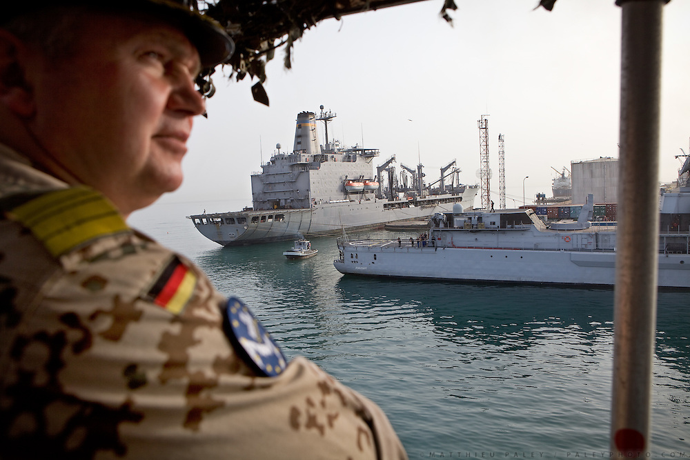 """Frigate Captain Nils Brandt returns to Djibouti harbour, passing French and US Army boats, after an operation carried out by the German navy...German Navy Force working with Operation Atalanta (EU anti-piracy mission) and OEF (Operation Enduring Freedom) on sea reconnaissance mission using a battleship called """"Schleswig-Holstein"""", to identify potential piracy activities off the coast of Somalia...The geostrategical and geopolitical importance of the Republic of Djibouti, located on the Horn of Africa, by the Red Sea and the Gulf of Aden, and bordered by Eritrea, Ethiopia and Somalia."""