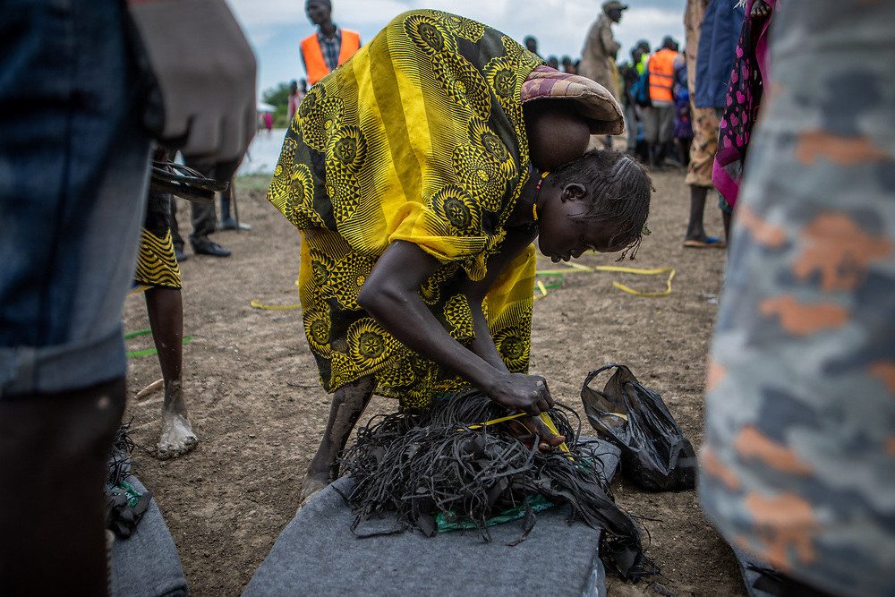 A woman with a baby strapped to her back collects a pile of household goods distributed to those who lost everything in devastating flooding - in Pibor, Boma State, South Sudan, on 6 November 2019 // Photo credit: UNICEF South Sudan/de la Guardia