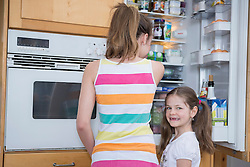 Sisters looking into refrigerator, smiling