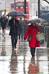 © Licensed to London News Pictures. 11/02/2013. London, UK. Commuters shelter under umbrellas during snowfalls on Whitehall in London today (11/09/13). Britain awoke to more snowfalls this morning, with up to 4 inches in some of the worst hit areas. Photo credit: Matt Cetti-Roberts/LNP