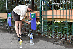 © Licensed to London News Pictures. 06/07/2018. LONDON, UK. A man queuing for day tickets in Wimbledon Park to the Wimbledon Tennis Championships takes advantage of filling water bottles.  Temperatures forecast to approach 30C mean that the majority have taken precautions to protect themselves from the sun by wearing sunglasses and sunhats.  Photo credit: Stephen Chung/LNP