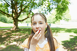 Portrait of a girl eating strawberry in park, Munich, Bavaria, Germany