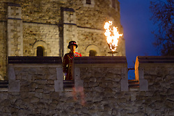© Licensed to London News Pictures. 21/04/2016. London, UK. The Chief Yeoman Warder lights a beacon at the Middle Drawbridge, accompanied by Yeoman warders (aka 'Beefeaters') in semi state dress, at the Tower of London, to celebrate the 90th birthday of Great Britain's Queen Elizabeth II. The Tower of London is one of thousands of sites across the UK that will light beacons tonight to celebrate the Queen's 90th birthday. Photo credit : Vickie Flores/LNP