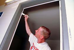 Young man painting door frame,