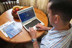 Man with hearing impairment studying on laptop computer.