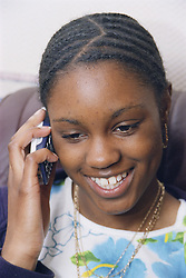 Teenage girl using mobile phone; laughing,