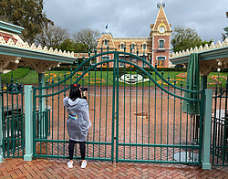 March 16, 2020, Anaheim, California, USA: A visitor to the Disneyland Resort takes a picture through a locked gate at the entrance to Disneyland in Anaheim. The entire Disneyland Resort is shutting down due to the coronavirus (COVID-19) outbreak. (Credit Image: © Jeff Gritchen/Orange County Register via ZUMA Wire)