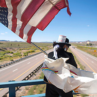 Nicole Walker holds both the United States flag and the Navajo Nation flag as she walks back and forth on the I-40 overpass to Fort Wingate Thursday. Walker held the flags to raise awareness for keeping the Fort Wingate land intact as Navajo as well as protesting the presidency of Russell Begaye.
