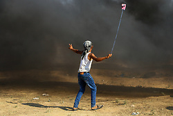 July 6, 2018 - A number of Palestinians demonstrators are injured during clashes with Israeli soldiers along the Gaza-Israeli border on the east of Gaza City, as the Great March of Return protests continue for the 15th Friday.  Dozens of Palestinian protesters gathered on the east of Gaza City burning tires and waving Palestinian flags with the Israeli soldiers firing gunshots and tear gas canisters to disperse the demonstrators, who replied with hurling stones at them. According to the Israeli authorities Palestinians released flammable kites into Israel causing fires to fields near the border. Since March 30th Gazans have held weekly Friday rallies defying the risks and since then at least 136 Palestinians have been killed and nearly 15 thousands injured by the Israeli army. Demonstrators have demanded their right of return to the land their ancestors were displaced or fled from, and they have also called for the lift of the siege on Gaza, enforced by Israel since 2007 (Credit Image: © Ahmad Hasaballah/IMAGESLIVE via ZUMA Wire)