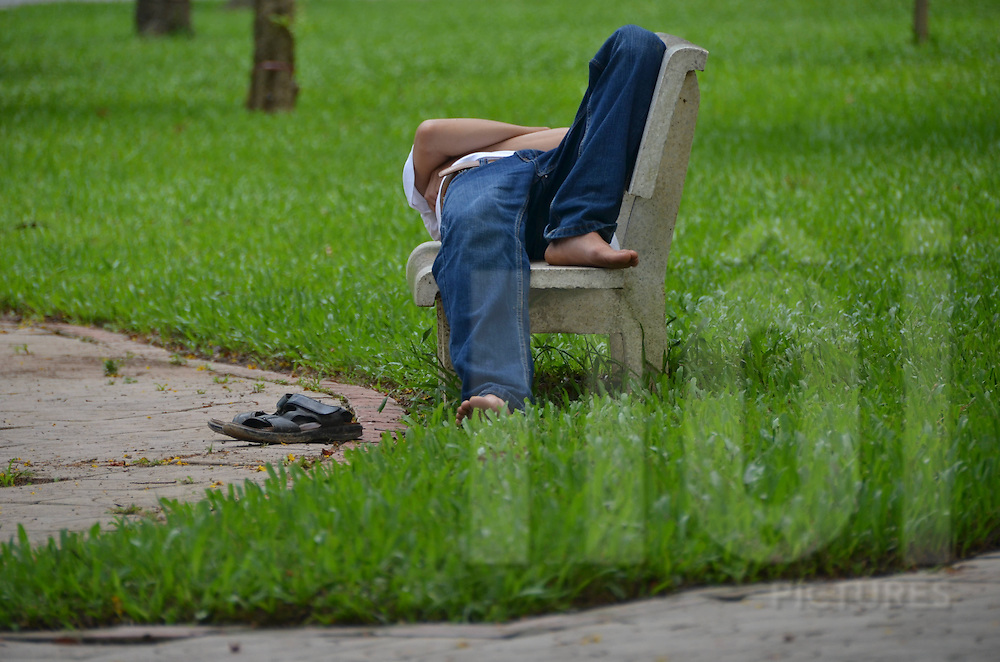 In Lenin Park in Hanoi, view of the man's legs while he's taking a nap on a bench. He wears a pair of jeans and has removed his shoes. There is grass around him.