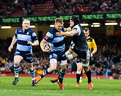 Gareth Anscombe of Cardiff Blues under pressure from James King of Ospreys<br /> <br /> Photographer Simon King/Replay Images<br /> <br /> Guinness PRO14 Round 21 - Cardiff Blues v Ospreys - Saturday 27th April 2019 - Principality Stadium - Cardiff<br /> <br /> World Copyright © Replay Images . All rights reserved. info@replayimages.co.uk - http://replayimages.co.uk