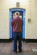 An elderly prisoner stands outside his cell door on the Vulnerable Prisoners Unit. HM Prison Wandsworth is a Category B men's prison at Wandsworth in the London Borough of Wandsworth, South West London, United Kingdom. It is operated by Her Majesty's Prison Service and is one of the largest prisons in the UK with a population over 1500 people. (photo by Andy Aitchison)