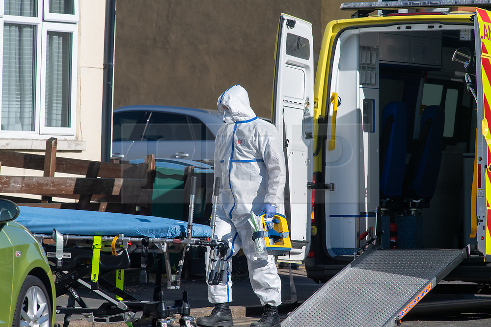 © Licensed to London News Pictures. 04/04/2020. Watford, UK. A paramedic wearing personal protective equipment (PPE) outside an address in Watford carries medial equipment. Paramedics responded to a medical incident in Watford, an ambulance an two incident response units attended   Photo credit: Peter Manning/LNP