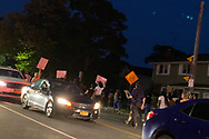 North Merrick, New York, U.S.  June 4, 2020. Black Lives Matter March heading east on Jerusalem Ave and then turning north onto Bellmore Avenue, toward East bound entrance to Southern State Parkway.  Shortly before protestors arrive, Nassau County Police officers park several patrol cars at intersection to stop and divert traffic to make path for march.