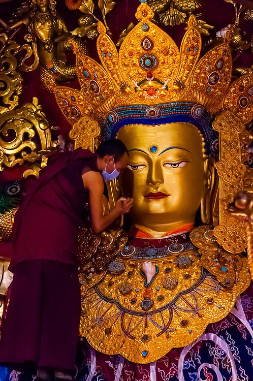 A monk touches up paint on a statue of Buddha, Samye Monastery, Chatang, Lhoka (Shannan) Prefecture, Tibet (Xizang), China. Samye is the first Buddhist monastery built in Tibet.