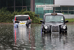 © Licensed to London News Pictures. 25/07/2021. London, UK. A London taxi sits abandoned in flood water as a Mercedes van is rescued in Stratford, east London. Heavy downpours and thunder and lightning have caused flooding in some parts of the UK today.. Photo credit: Kois Miah/LNP