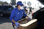 Volunteers distribute meals at the Los Angeles Dodgers Foundation 16th annual Thanksgiving Turkey Giveaway at Dodger Stadium, Thursday, Nov. 19, 2020, in Los Angeles.