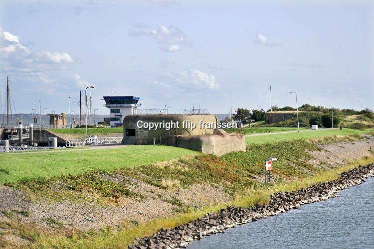 Nederland, kornwerderzand, 30-8-2018De bunkers van de stelling Kornwerderzand zijn een oorlogsmuseum en voor publiek toegangkelijk. Tijdens de duitse inval en aanval in 1940 hield ze stand tot de overgave 15 mei.Na de ingebruikname van de Lorentzsluizen in 1932 werd in 1932-1933 de stelling Kornwerderzand gebouwd.Er werd gekozen voor de gespreide opstellingen van diverse kleine verdedigingswerken. De kazematten werden gemaakt van gewapend beton aangevuld met pantserstaal op de meest kwetsbare plekken.  Foto: Flip Franssen