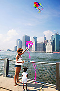 Mother and Daughter fly a kite off the East River at Brooklyn Bridge Park, facing the Manhattan Skyline and Staten Island Ferry Terminal, during this annual festival