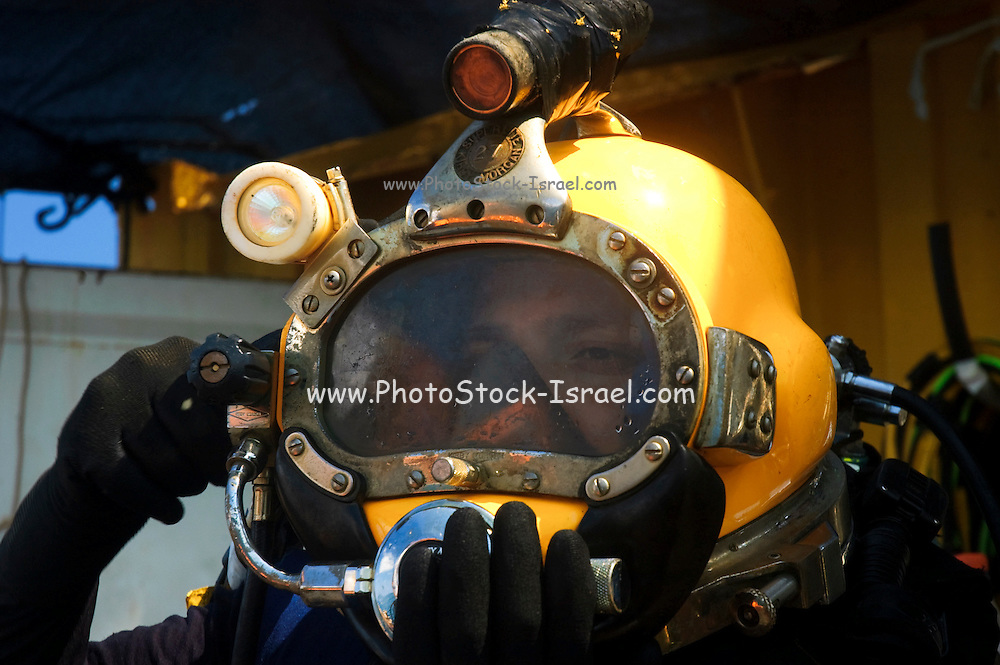 """Israel, Bay of Haifa, Offshore rig salvages the remains of the Israeli cargo vessel """"Shelly"""" that sunk 3km from the harbour after a collision with a passenger ship on August 31 2007. Commercial diver gets ready for a dive in the Mediterranean sea. Cables from the surface are supplying electrical power for the lights, and allowing communication with the surface. The diver is using a helmet connected to an air supply on his back"""