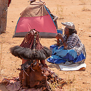 Herero and Himba women at a funeral gathering, tents and huts can be seen in the background. Kaokoland, Namibia