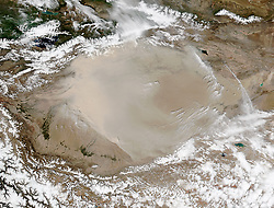 The Taklimakan desert is one of the driest, most barren expanses on Earth. Flanked by mountain ranges on three sides and parched by the resulting rain shadow, parts of the Tarim Basin receive no more than 10 millimeters (0.4 inches) of rain per year. It is no surprise that plant life is scarce. With little vegetation to hold sand in place, some 85 percent of the Taklimakan consists of shifting sand dunes. Only the dune fields of Saudi Arabia's Rub' al Khali cover a larger area. Taklimakan's dunes can soar up 200 to 300 meters (650 to 900 feet).<br /> With so much sand and so little vegetation or moisture, dust storms are a regular occurrence, particularly in the spring. On May 1, 2016, the Visible Infrared Imaging Radiometer Suite (VIIRS) on the Suomi NPP satellite captured this natural-color image of northeasterly winds pushing a wall of dust southwest across the Tarim Basin.<br /> The Tarim Basin is bordered by the Kunlun Shan mountains to the south and the Tian Shan mountains to the north. (The Tian Shan is covered with snow and partly obscured by clouds in this image.) The basin opens up on its eastern edge, but that is not generally a way out for dust. Prevailing low-altitude winds almost always blow from the east, keeping most dust below 5 kilometers (3 miles) - about the height of the mountain ranges - and trapped within the basin. In spring, strong surface winds can sometimes lift dust up to 10 kilometers (6 miles). These particles can then be transported by higher-altitude winds that send them across China and the Pacific. In this case, however, the dust appears to be relatively low in the atmosphere.<br /> Dust storms can lead to public health problems in populated areas downwind by transporting small particles, bacteria, and viruses that infiltrate human respiratory systems. Dust storms also affect Earth's climate by scattering and absorbing incoming solar radiation and changing the properties of clouds.<br /> References and Related Reading<br /> Ge, J. M
