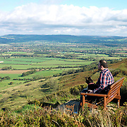 A man sits with his dog on a bench overlooking a view of the North York Moors, North Yorkshire, UK