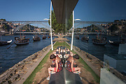 A symmetrical reflection of afternoon sunbathers realaxing on the bank of the Douro river with the panorama of the Ponte de Dom Luis I bridge and the city of Porto behind, on 20th July, in Porto, Portugal. The Dom Luís I or Luiz I Bridge is a double-decked metal arch bridge that spans the Douro River between the cities of Porto and Vila Nova de Gaia in Portugal. At the time of construction its span of 172 m was the longest of its type in the world.