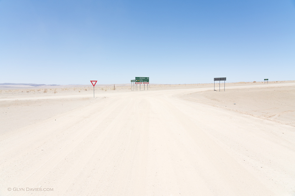 Nominee in 14th (2021) International Colour Awards (Fine Art category)<br /> <br /> After miles of dirt-road driving through vast empty desert landscape, it was quite a shock to see anything man-made other than the road itself, let alone signs that indicated that civilisation actually existed somewhere amongst this isolation. It was a blast of 'normality' and 'order' yet seemed utterly incongruous to our surroundings. I loved the surreality of it all.
