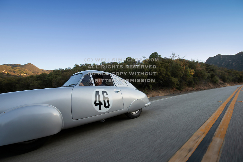 Image of Cameron Healy driving his silver 1951 Porsche Gmund 356 SL 063 coupe which won its class at the 1951 Le Mans in France, on Mulholland Drive in Hollywood, California, America west coast. The Gmund was restored to its original look as it had finished Le Mans by Rod Emory and his team at Emory Motorsports in North Hollywood, California. Photo by Randy Wells